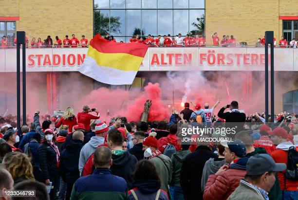 """Hundreds of Union supporters xheer and light flares outside the stadium """"Alte Foersterei"""" as the team appears on the balcony after the German first..."""