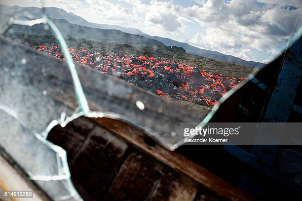 Hundreds of used life vests are reflected in a broken window on a makeshift rubbish dump hidden in the hills above the town on March 10 2016 in...