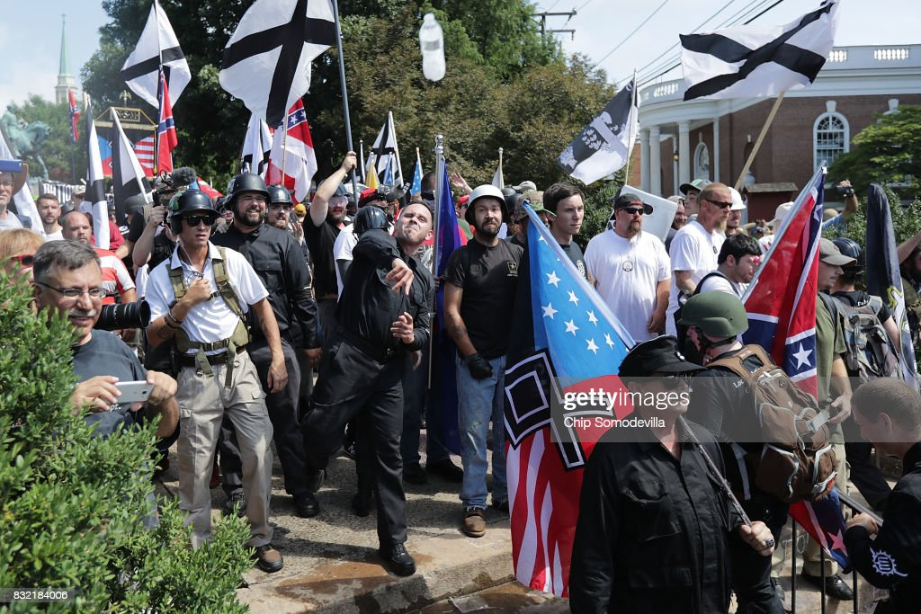 Hundreds of white nationalists, neo-Nazis, KKK and members of the 'alt-right' hurl water bottles back and forth against counter demonstrators on the outskirts of Emancipation Park during the Unite the Right rally August 12, 2017 in Charlottesville, Virginia. After clashes with anti-facist protesters and police the rally was declared an unlawful gathering and people were forced out of Lee Park, where a statue of Confederate General Robert E. Lee is slated to be removed.
