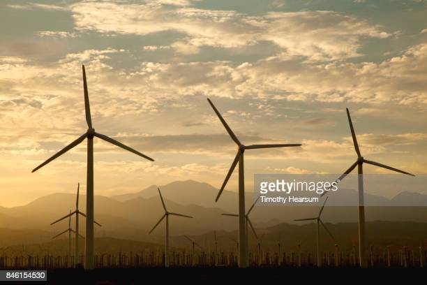 hundreds of wind generators with mountains, sky and clouds beyond - timothy hearsum stock photos and pictures