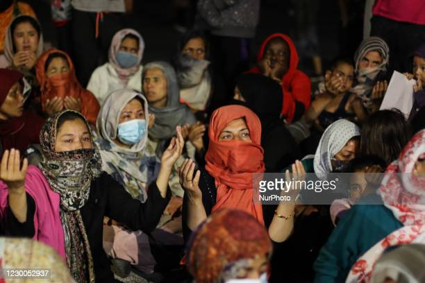 Hundreds of women and girls are seen praying on the road after the sunset, at the makeshift tent site that was built roadside after the fire of Moria...