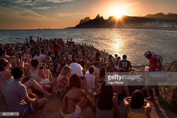 Hundreds of young people sitting on the Arpoador rocks enjoy the sunset and the relaxed atmosphere.