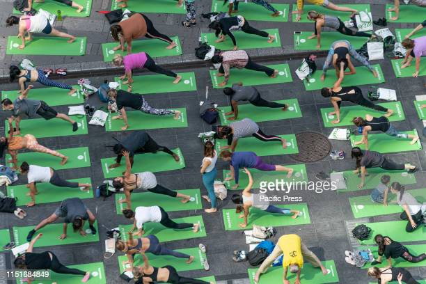Hundreds yoga enthusiasts participate in mass yoga class on Times Square to celebrate the summer solstice and mark World Yoga Day