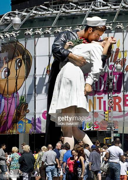 Hundres gather in Times Square to view the sculpture at the site of the historic LIFE Magazine cover photograph, of an unidentified sailor kissing...