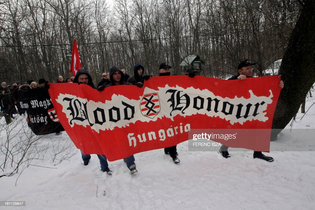 Hungarian activists of the neo-Nazi Blood and Honour group hold flags and march on the 'Norma-fa' hill in Budapest on February 9, 2013. More than 500 people attended the event to commemorate the 68th anniversary of the ill-fated escape attempt of Nazi German and Hungarian soldiers from Buda Castle, which was besieged on 11 February 1945 by the Soviet Red Army at the end of World War II. Participants placed a German WWII helmet and wood cross in the snow.