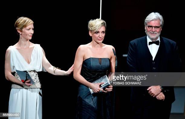 Hungarian actress Alexandra Borbely holds her trophy flanked by German actress Sandra Hueller and Austrian actor Peter Simonischek after receiving...