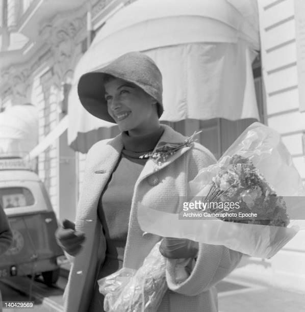 Hungarian actress Eva Bartok holding a bouquet Lido Venice 1955