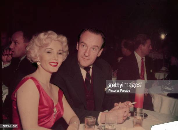 Hungarian actress Zsa Zsa Gabor smiles for the camera while sitting at a table with her husband Russianborn actor George Sanders 1950s