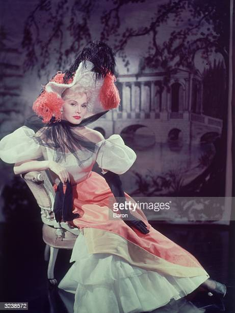 Hungarian actress Zsa Zsa Gabor wearing an elaborate costume with a feathered hat and black gloves possibly from the 1952 film 'Moulin Rouge'