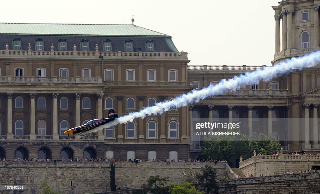 Hungarian aerobatics pilot and world champion air racer Peter Besenyei flies with his aircraft under the oldest Hungarian bridge, the 'Chain Bridge' and over the Danube River in Budapest on May 1, 2013 during an air show.