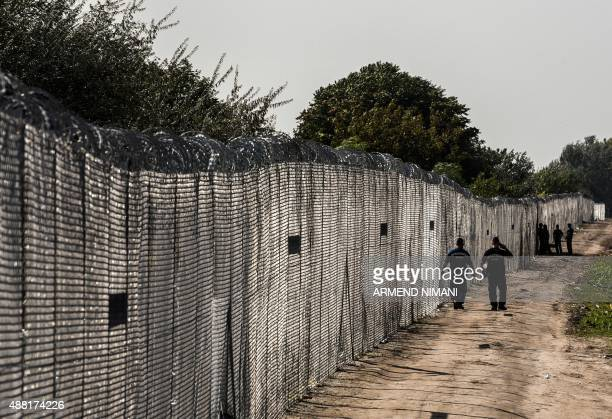 Hungarian border police patrol along a barbed wire fence at the Hungarian border with Serbia near the town of Horgos on September 14 2015 Many of the...