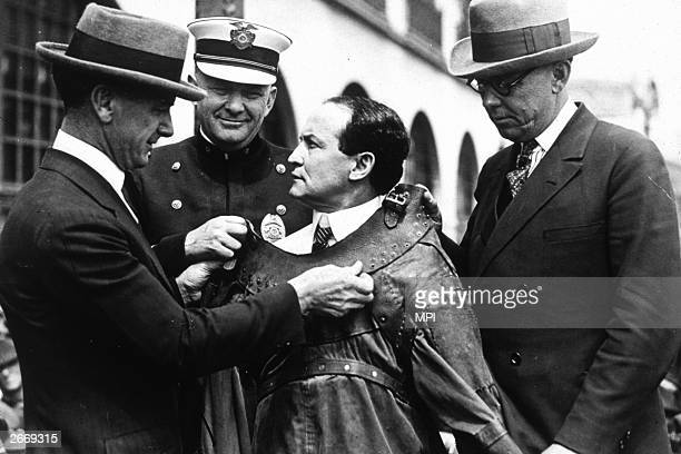 Hungarian born magician and escapologist Harry Houdini being fitted into an escape proof suit