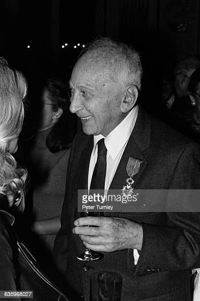 Hungarian born photographer Andre Kertesz smiles as he talks with a woman after being awarded the Legion of Honor He wears the medal he was presented...