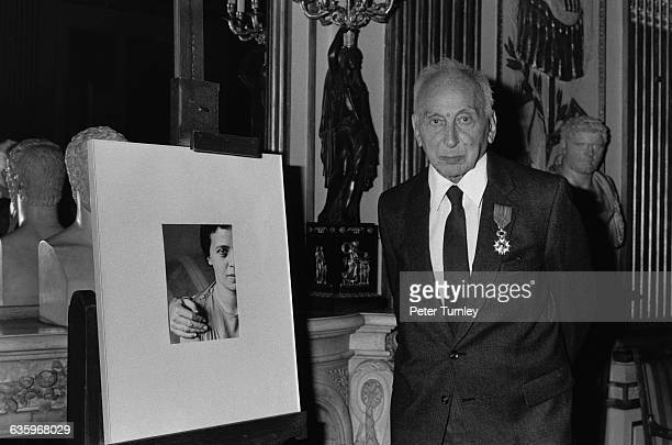 Hungarian born photographer Andre Kertesz stands beside a portrait of his wife which he photographed Kertesz wears the medal he was awarded by the...