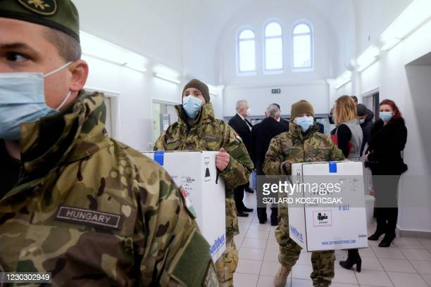 Hungarian carry boxes from the first shipment of Pfizer-BioNTec vaccines against the novel coronavirus at the South-Pest Central Hospital in Budapest...