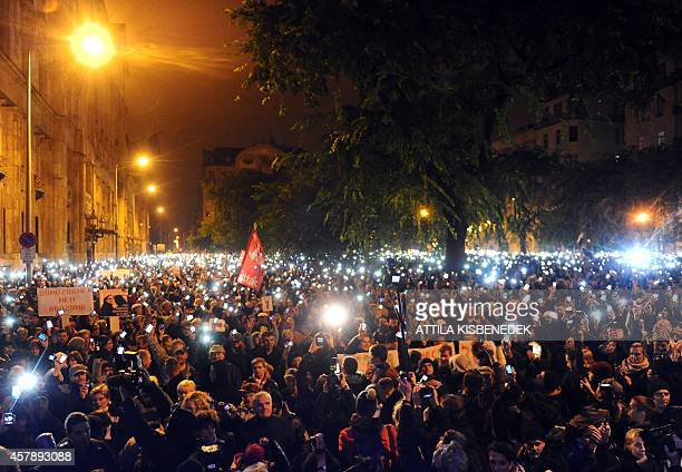 Hungarian citizens lift their mobile phones to protest against the goverment's new tax plan for the introduction of the internet tax next year in...
