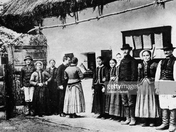 Hungarian composer and pianist Bela Bartok listens to folk music on a phonograph with villagers Darazs Hungary 1907