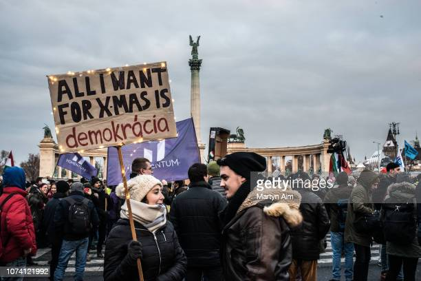 Hungarian couple hold a sign that reads 'All I Want For Christmas Is Democracy' as thousands of protesters from a wide range of political and civil...