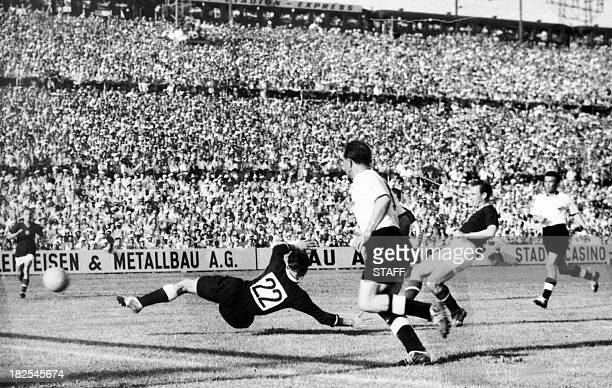 Hungarian forward Nandor Hidegkuti scores the fifth goal for his team past German goalkeeper Heiner Kwiatkowski as Werner Kohlmeyer looks on during...