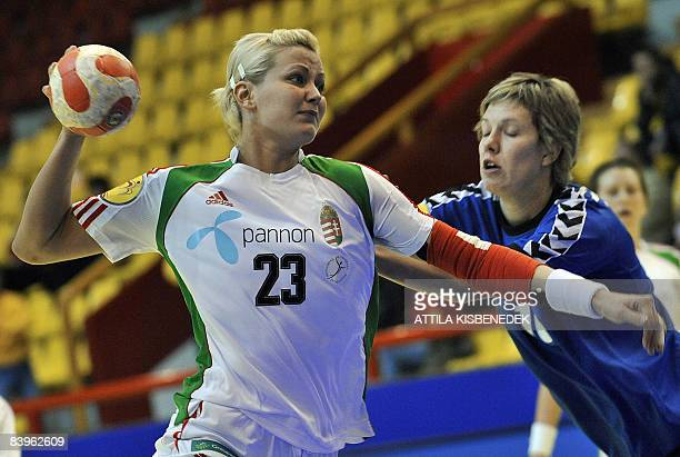 Hungarian Gabriella Szucs scores a goal against Ukrainian Maryna Vergeliuk during the 8th Women's Handball European Championships match on December 9...