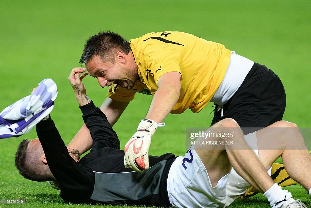 Hungarian goalkeeper Szabolcs Balajcza (R) and Peter Kabat (L) of TE Ujpest celebrate their victory after the Hungarian Cup final football match VTK Disosgyor vs TE Ujpest on May 25, 2014 at the Puskas stadium in Budapest. Ujpest won the match 6-5 after a penalty shootout.