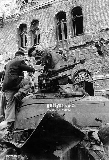 Hungarian insurgents jumping on a just captured Soviet tank Budapest November 1956