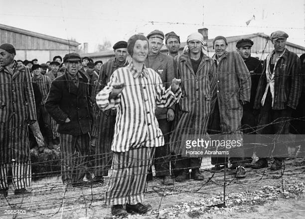 A Hungarian Jewish boy in his prison suit of blue and white stripes smiles over the barbed wire at Dachau concentraion Camp He was expecting to be...