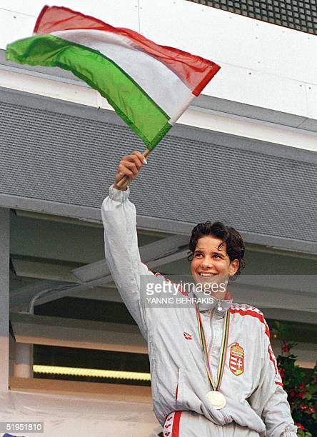 Hungarian Krisztina Egerszegi waves the Hungarian flag 31 July 1992 at the medal ceremony after she won the gold in the 200m backstroke at the 1992...