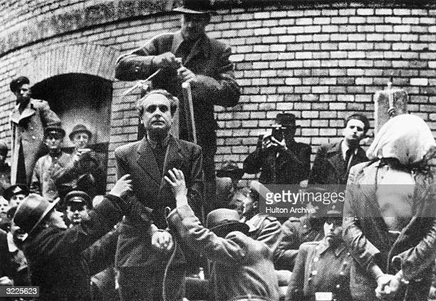 Hungarian Nazi leader Ferenc Szalasi stands next to an executed man with his hands bound a sack over his head and an open shirt while a man behind...