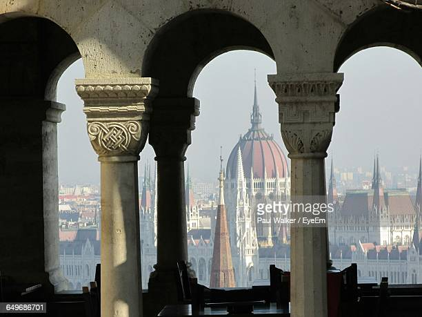 Hungarian Parliament Building Viewed Through Arches In Budapest