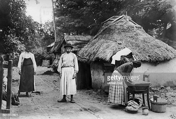 Hungarian peasants in front of a thatched cottage in the village of Füzesabony undated probably around 1910