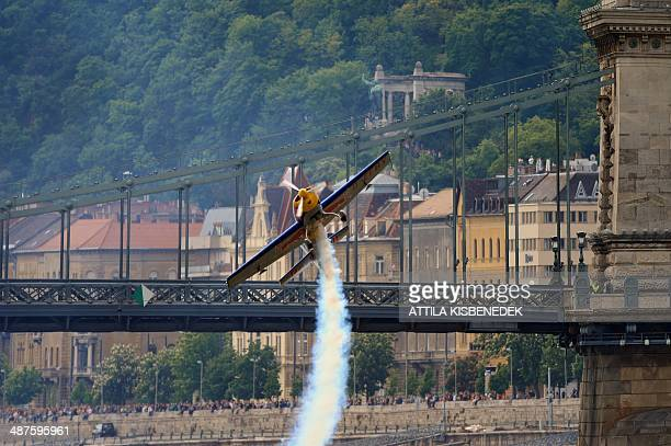 Hungarian pilot and world champion Peter Besenyei flies under the oldest Hungarian bridge the 'Lanchid' with his 'Corvus Racer' plane on May 1 2014...