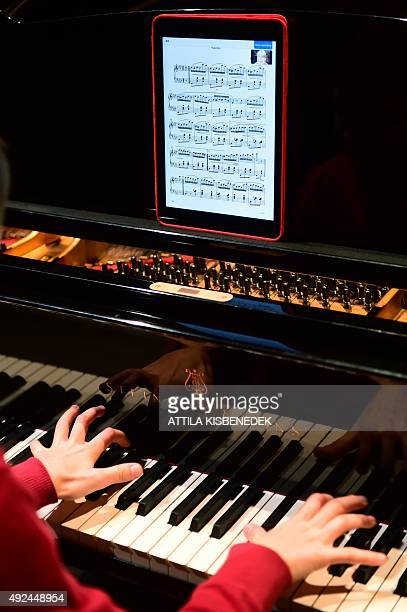 Hungarian pofessional pianist Misi Boros plays from a tablet with a sheet of a classical music in the concert hall of Budapest Music Center on...
