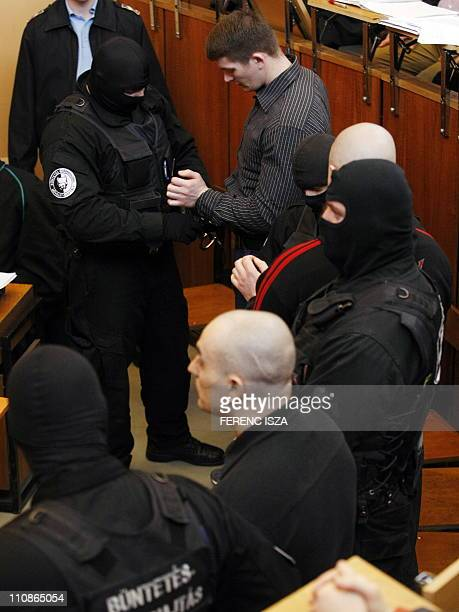 Hungarian police escort murder suspect in the death of two Roma Istvan Kiss and Istvan Csontos in the Pest County Court in Budapest on March 25...