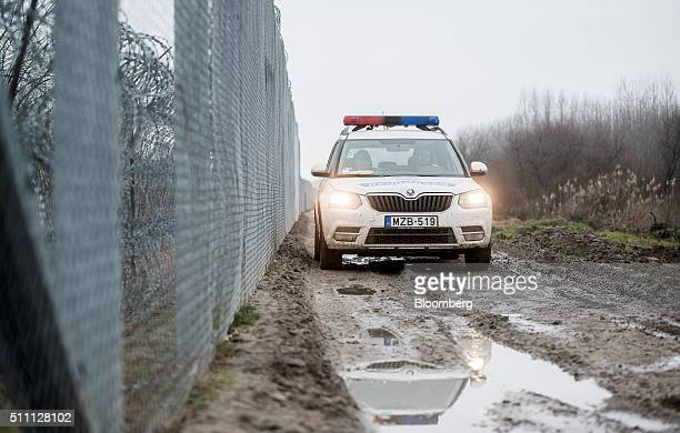 A Hungarian police force automobile drives by the razor wired security fences on the HungarianSerbian border near Roszke Hungary on Wednesday Feb 17...