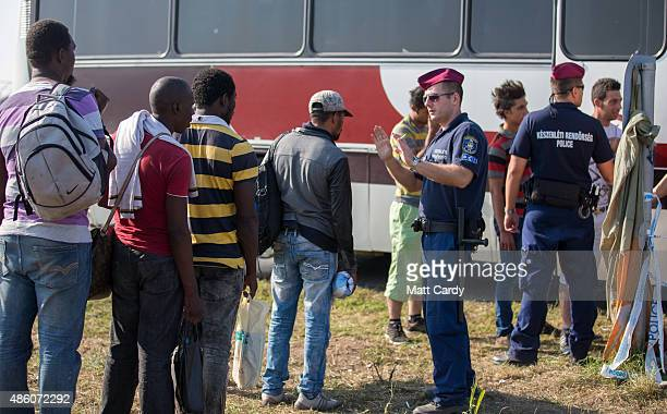 Hungarian police officer controls a queue of migrants as they board a bus to take them to a reception centre after they crossed the border from...
