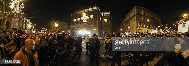 Hungarian police officers stand in front of the State Opera House of Budapest as tens of thousands protest against Hungary's new constitution which...