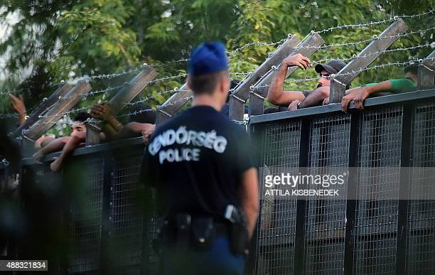 Hungarian police officers stand on guard in front of a metal gate at the closed M5 highway to block circulation of migrants at the Hungarian-Serbian...