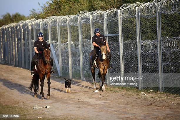Hungarian police on horses patrol the HungarianSerbian border fence after the open rail track crossing was closed on September 14 2015 in Roszke...