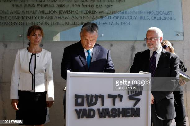 Hungarian Prime Minister Viktor Orban and his wife Aniko Levai sign the guest book on July 19 2018 during their visit to the Yad Vashem Holocaust...