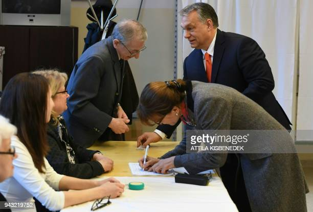Hungarian Prime Minister Viktor Orban and his wife Aniko Levaiarrives to vote at a polling station located ina school in Budapest on April 8 2018...