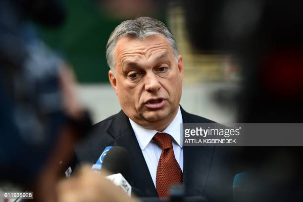 Hungarian Prime Minister Viktor Orban answers to the journalists in front of a polling station at a school in Budapest on October 2 2016 Hungarians...