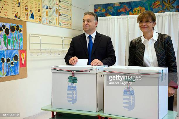 Hungarian Prime Minister Viktor Orban casts his vote with his wife Aniko Levai during local elections at a polling station in Budapest Hungary on...