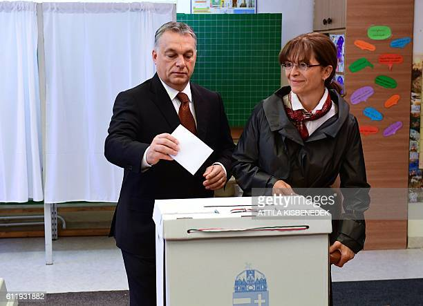 Hungarian Prime Minister Viktor Orban casts his vote with his wife Aniko Levai at a polling station of a local school in Budapest on October 2 2016...