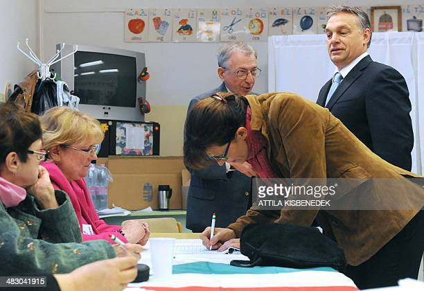 Hungarian Prime Minister Viktor Orban chats with an election offical as his wife Aniko Levai signs a document in a polling station of a local school...