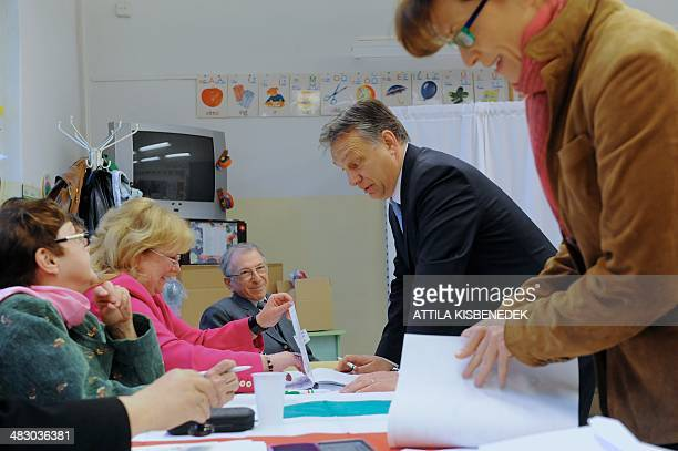 Hungarian Prime Minister Viktor Orban chats with an election officals as his wife Aniko Levai holds ballot papers in a polling station of a local...