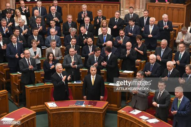 Hungarian Prime Minister Viktor Orban is applauded by MPs as he takes the oath for a third straight term as Hungarian prime minister on May 10 2018...