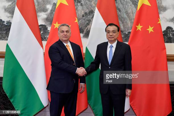 Hungarian Prime Minister Viktor Orban left shakes hands with Chinese Premier Li Keqiang as they pose for media before their meeting on April 25 2019...