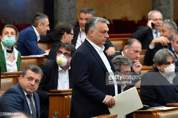 Hungarian Prime Minister Viktor Orban walks near other representatives during a vote about the government's bill on the protection against the new...