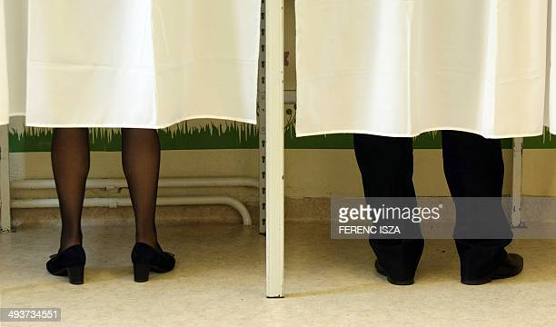 Hungarian Prime Minister Viktor Orban with his wife Aniko Levai stand in a voting booth at a polling station for the European Parliament elections on...